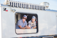 Men wearing chefs hats looking out of catering van hatch