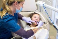 Girl in dentist chair having dental examination