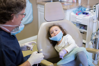 Girl in dentist chair watching dentist prepare dental equipment