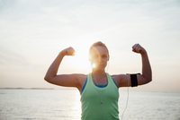 Woman wearing activity tracker, arms raised flexing muscles looking at camera