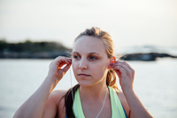 Woman inserting earbuds looking away