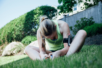 Woman wearing activity tracker sitting on grass stretching looking down