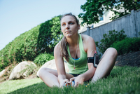 Woman wearing activity tracker sitting on grass looking away
