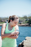 Woman wearing earbuds looking at activity tracker on arm
