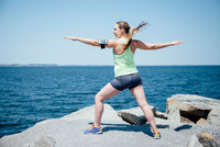 Full length rear view of woman wearing activity tracker on rocks by ocean, arms open exercising