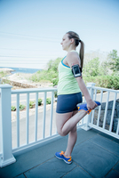 Rear view of woman wearing activity tracker on balcony stretching leg