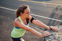High angle view of woman wearing activity tracker stretching against concrete block