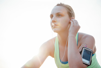 Woman wearing activity tracker inserting earbud looking away