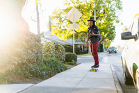 Woman skateboarding on pavement, looking at smartphone