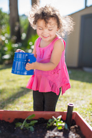 Young girl in garden, holding watering can, watering plants in tub, smiling