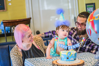 Young adult parents with baby son at first birthday party