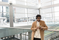 Young businessman selecting smartphone music in train station