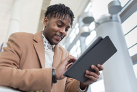 Young businessman in train station using digital tablet touchscreen
