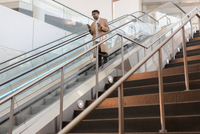 Young businessman moving down train station escalator with takeaway coffee