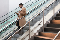 Young businessman moving down train station escalator reading smartphone