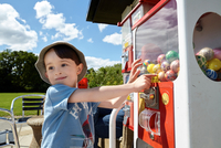 Happy boy pointing at gumball machine