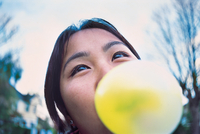 Close up of young woman blowing yellow bubble gum bubble