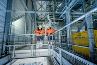 Workers on high level walkway in gas-fired power station