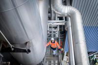 Worker inspecting pipes in gas-fired power station