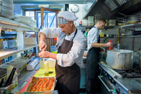 Chef preparing tomatoes in traditional Italian restaurant kitchen
