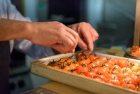 Chef preparing tomatoes in traditional Italian restaurant kitchen, close up