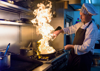 Chef with pan of flames in traditional Italian restaurant kitchen