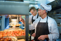 Chef checking order in traditional Italian restaurant kitchen