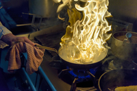 Chef with pan of flames in traditional Italian restaurant kitchen, close up