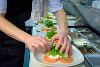 Chef preparing salad dish in traditional Italian restaurant kitchen, close up