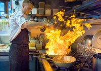 Chef pouring brandy into flaming pan in traditional Italian restaurant kitchen