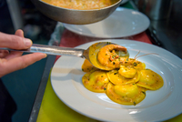 Chef plating up lobster ravioli in traditional Italian restaurant kitchen, close up