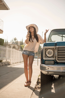 Young woman chatting on smartphone beside truck