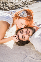Head and shoulders of couple lying on beach face to face 11015274927| 写真素材・ストックフォト・画像・イラスト素材|アマナイメージズ
