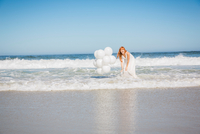 Woman ankle deep in ocean wearing white dress holding balloons