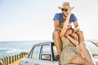 Mid adult couple sitting on top of car on coast road, Cape Town, South Africa