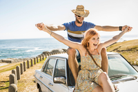 Mid adult couple with open arms on top of car on coast road, Cape Town, South Africa