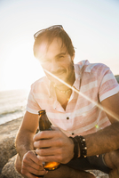 Portrait of mid adult man with bottle of beer on beach at sunset, Cape Town, South Africa