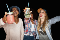 Young women holding mason jars arms raised open mouthed smiling