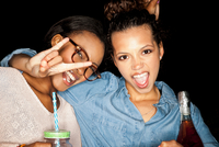 Young woman arm around friend looking at camera open mouthed doing rock sign
