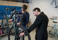 Two men checking bicycle in hipster bike repair cafe