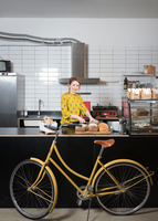 Portrait of waitress slicing bread at hipster bike repair cafe