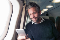 Mid adult man on airplane, using smartphone