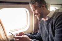 Mid adult man on airplane, using smartphone 11015275505| 写真素材・ストックフォト・画像・イラスト素材|アマナイメージズ