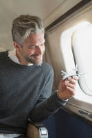 Mid adult man on airplane, holding model airplane, smiling