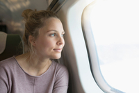 Young woman on airplane, looking out of window