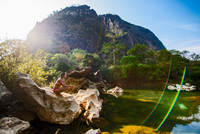 Young woman crouching on rock beside Thafalang River, looking at view, Thakhek, Khammouane, Laos