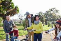 Multi generation family in park on with bicycles