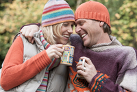 Heterosexual couple outdoors, holding hot drinks, smiling