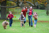 Family fooling around in park, throwing autumn leaves