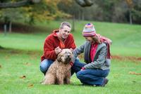 Heterosexual couple in park, crouching, stroking dog 11015275912  写真素材・ストックフォト・画像・イラスト素材 アマナイメージズ